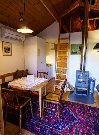 Seebungalow Wohnbereich mit Esstisch und Kaminofen, Schlafloft