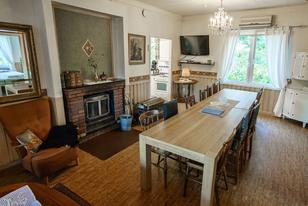 Paradiesvilla Wohnzimmer mit Esstisch, Sofagruppe und Kaminofen