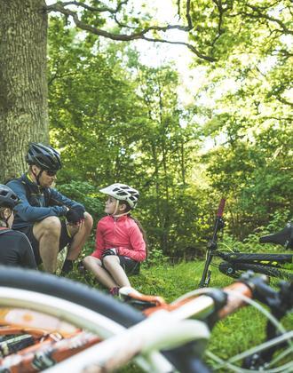Vater mit Tochter machen Pause während Mountainbiketour