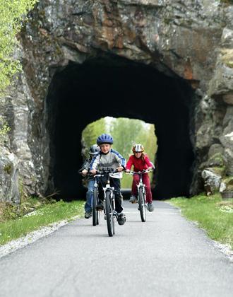 Kinder fahren durch einen Tunnel auf dem autofreien Radweg