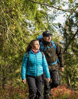 ein Paar wandert auf dem Åsundenleden durch den Wald